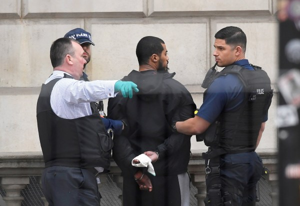 FILE PHOTO: Khalid Mohammed Omar Ali is held by police in Westminster he was arrested on Whitehall in central London, Britain, April 27, 2017. Ali was found guilty of preparing acts of terrorism, June 26, 2018. REUTERS/Toby Melville/File Photo