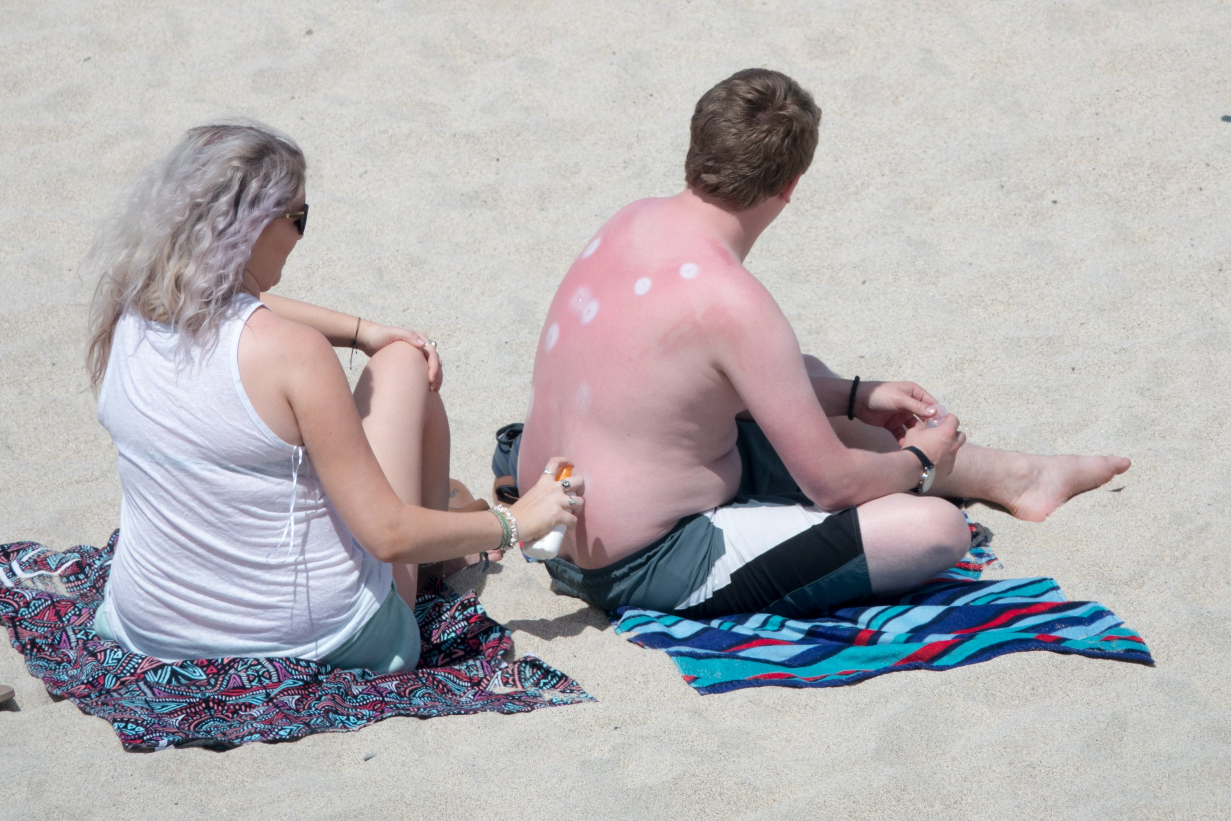 ST IVES, ENGLAND - JUNE 27: A woman applies sun lotion to a man's back as they enjoy the fine weather on Porthmeor Beach in St Ives on June 27, 2018 in Cornwall, England. Parts of the UK continue to bask in heatwave weather with the hottest temperatures of the year recorded this afternoon, 89F (31.9C) reached in Portmadog in Wales. Meanwhile 88F (30.8C) was recorded in Northern Ireland, making today the hottest day in the country's history. (Photo by Matt Cardy/Getty Images)