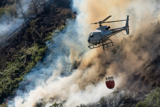 ? Licensed to London News Pictures. 29/06/2018. Rheidol Valley, UK. A helicopter dumps water over a forest fire that started on Tuesday 26the June is still burning and smouldering for a fourth day along the steep hillsides of the Rheidol Valley, a few miles inland of Aberystwyth in Mid Wales. Photo credit: Keith Morris/LNP