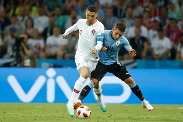 Uruguay's midfielder Lucas Torreira (R) vies for the ball with Portugal's forward Cristiano Ronaldo during the Russia 2018 World Cup round of 16 football match between Uruguay and Portugal at the Fisht Stadium in Sochi on June 30, 2018. / AFP PHOTO / Odd ANDERSEN / RESTRICTED TO EDITORIAL USE - NO MOBILE PUSH ALERTS/DOWNLOADSODD ANDERSEN/AFP/Getty Images