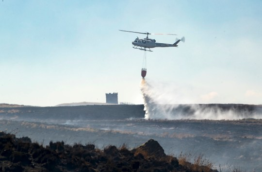 A helicopter dumps water, as firefighters continue to work on Winter Hill near Bolton. PRESS ASSOCIATION Photo. Picture date: Tuesday July 3, 2018. Fire chiefs declared a major incident on Saturday after two large-scale blazes either side of Winter Hill near Bolton merged because of increased wind speed. See PA story FIRE Moors. Photo credit should read: Danny Lawson/PA Wire
