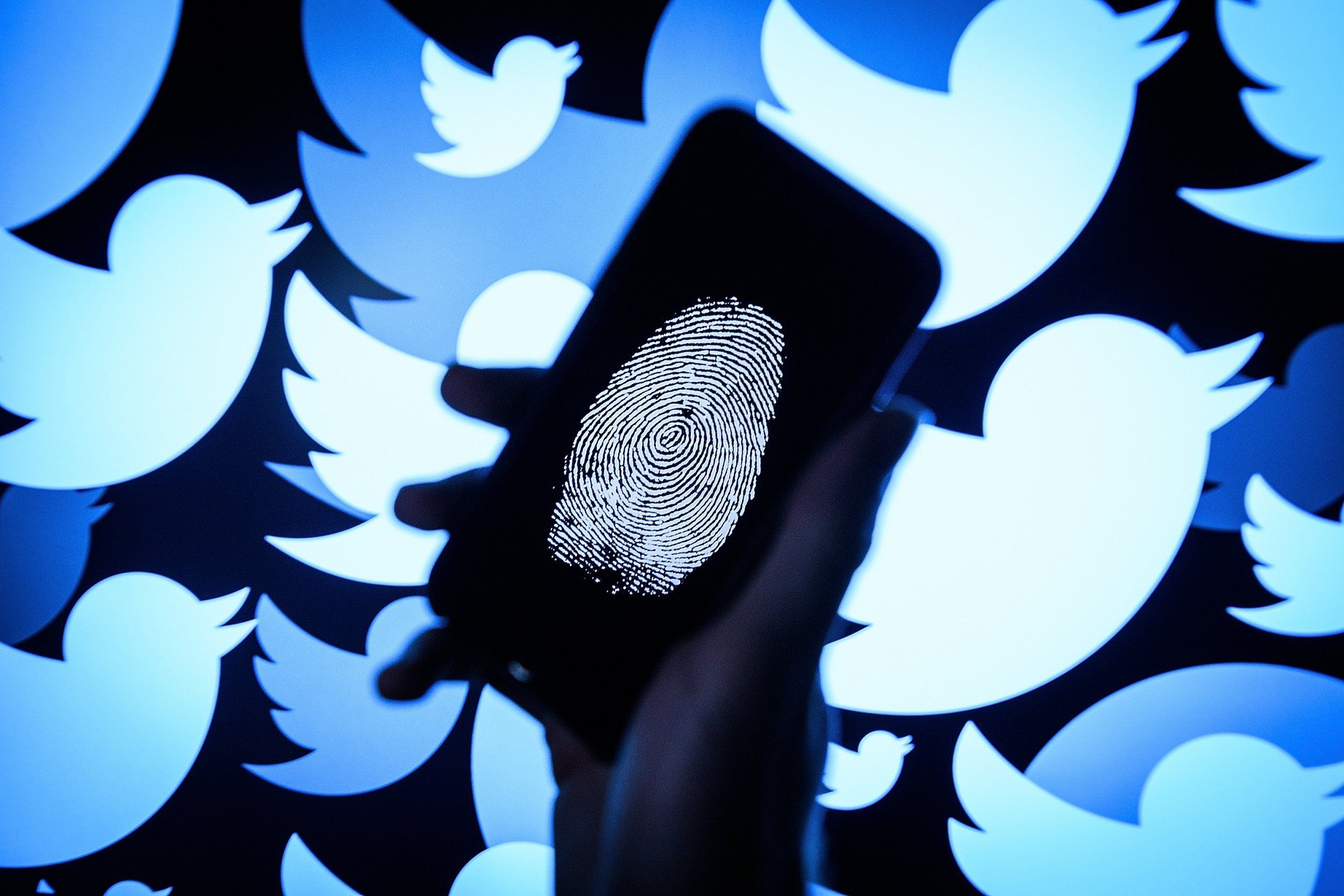 LONDON, ENGLAND - AUGUST 09: In this photo illustration, a thumbprint is displayed on a mobile phone as the logo for the Twitter social media network is projected onto a screen on August 09, 2017 in London, England. With around 328 million users worldwide, Twitter has gone from a small start-up in for the public 2006 to a broadcast tool of politicians and corporations in 2017. (Photo by Leon Neal/Getty Images)