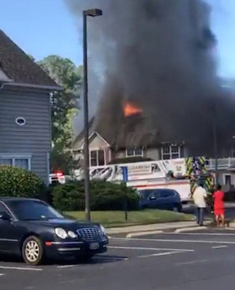 People watch as firefighters battle flames at a site where a helicopter has crashed into a building in Williamsburg, Virginia, U.S. July 8, 2018, in this still image taken from a video obtained from social media. MANDATORY CREDIT. Scott Gorslene/via REUTERS THIS IMAGE HAS BEEN SUPPLIED BY A THIRD PARTY. NO RESALES. NO ARCHIVES MANDATORY CREDIT.