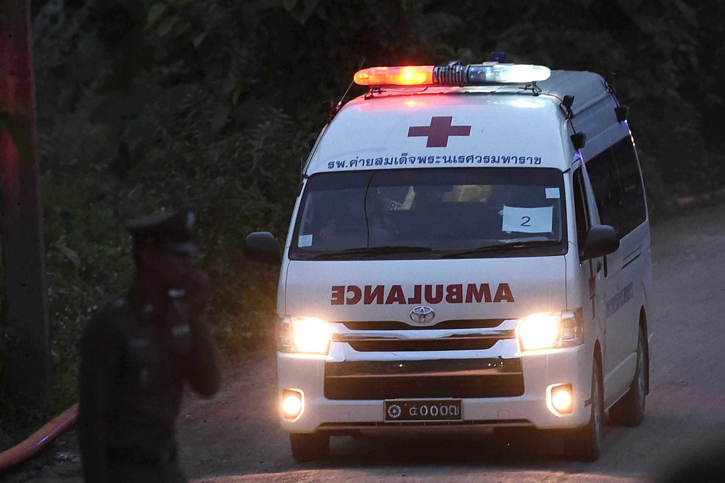 "An ambulance exits from the Tham Luang cave area as rescue operations continue for those still trapped inside the cave in Khun Nam Nang Non Forest Park in the Mae Sai district of Chiang Rai province on July 9, 2018. Rescue workers dived deep inside a flooded Thai cave for a second straight day on July 9 in a treacherous bid to save a trapped group of young footballers, with the mission chief promising more ""good news"" after four of the 13 were saved. / AFP PHOTO / YE AUNG THUYE AUNG THU/AFP/Getty Images"