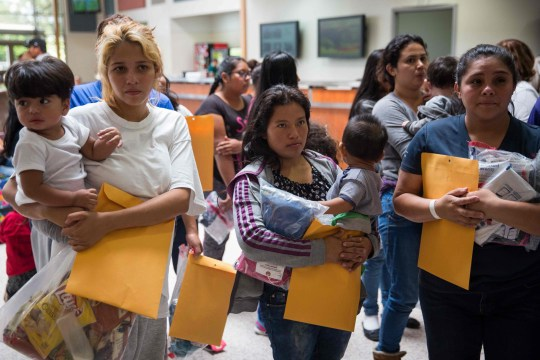 """(FILES) In this file photo taken on June 17, 2018 immigrants wait to head to a nearby Catholic Charities relief center after being dropped off at a bus station shortly after release from detention through """"catch and release"""" immigration policy in McAllen, Texas. A US judge on July 9, 2018 gave the government more time to reunite migrant children aged five or younger with their parents separated as a consequence of a """"zero tolerance"""" policy, US media reported. / AFP PHOTO / Loren ELLIOTTLOREN ELLIOTT/AFP/Getty Images"""