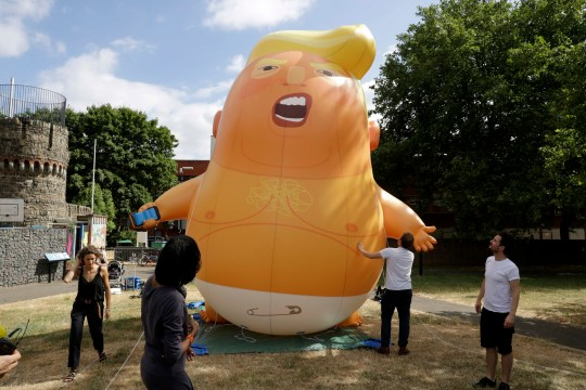 In this photo taken on Tuesday, July 10, 2018, a six-meter high cartoon baby blimp of U.S. President Donald Trump stands inflated during a practice session in Bingfield Park, north London. Trump will get the red carpet treatment on his brief visit to England that begins Thursday: Military bands at a gala dinner, lunch with the prime minister at her country place, then tea with the queen at Windsor Castle before flying off to one of his golf clubs in Scotland. But trip planners may go out of their way to shield Trump from viewing another aspect of the greeting: an oversize balloon depicting the president as an angry baby in a diaper that will be flown from Parliament Square during what are expected to be massive gatherings of protesters opposed to Trump???s presence. (AP Photo/Matt Dunham)