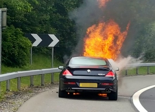 Andrew Lindsay's BMW bursting into flames. A DAD-of-one?s BMW 6 Series erupted in a fireball on a motorway and trapped him inside the burning car ? when the locks jammed. See NTI story NTIBMW. Andrew Lindsay, 45, desperately tried to escape the motor when it burst into flames while he was travelling at 70mph on the M6 Toll Road. He managed to shoulder barge the driver?s door open and leap from the car moments before the engine exploded and melted the tyres to the road. Andrew, a copy editor from Whittington, Staffs., was on his way to see family in North Wales when the blaze broke out on June 1.