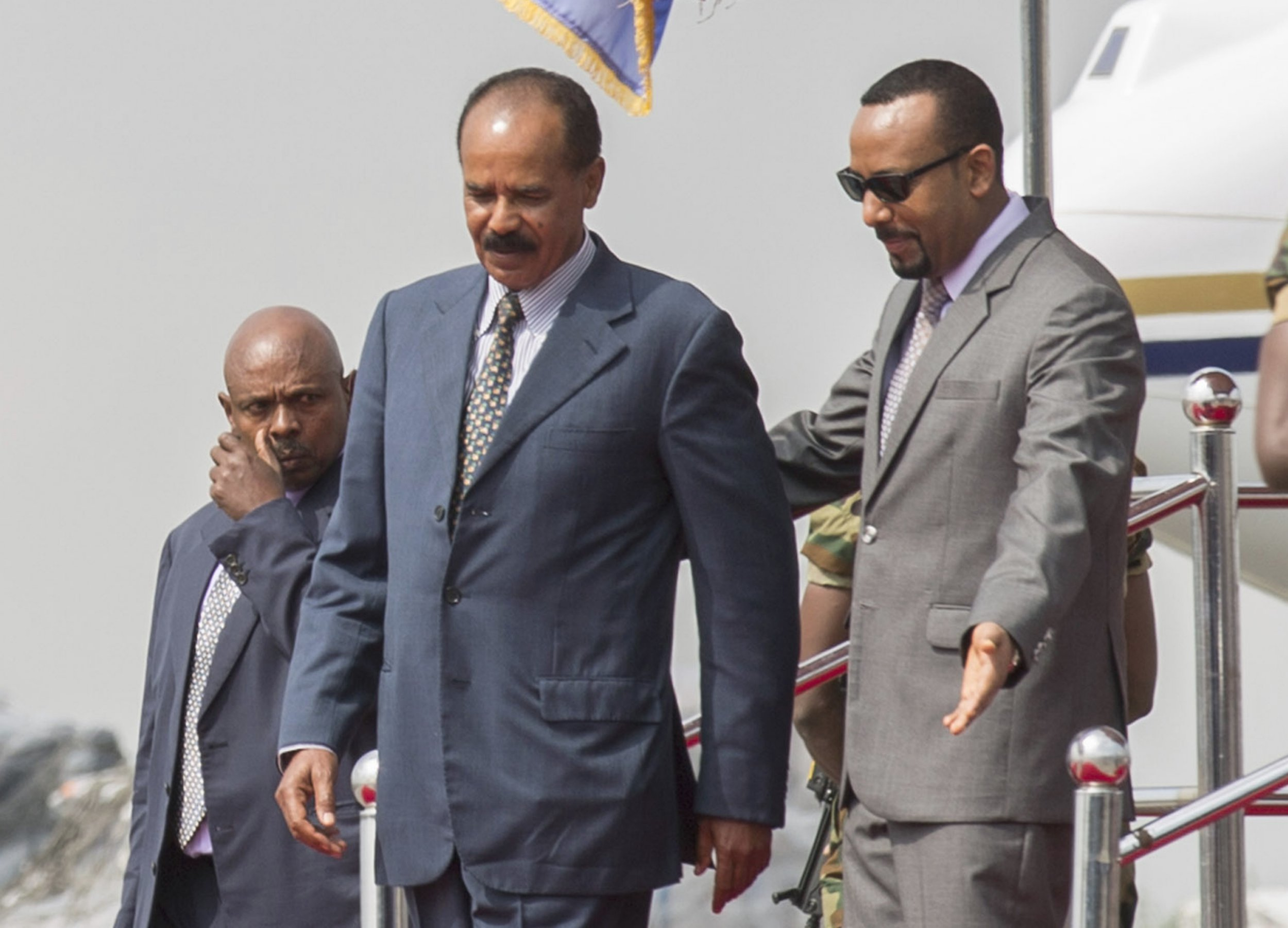 Eritrean President Isaias Afwerki, foreground left is welcomed by Ethiopia's Prime Minister Abiy Ahmed upon his arrival a Addis Ababa International Airport, Ethiopia, Saturday, July 14, 2018. To dancing and cheers, Eritrea's longtime president arrived in Ethiopia for his first visit in 22 years on Saturday amid a dramatic diplomatic thaw between the once-bitter rivals. (AP Photo Mulugeta Ayene)