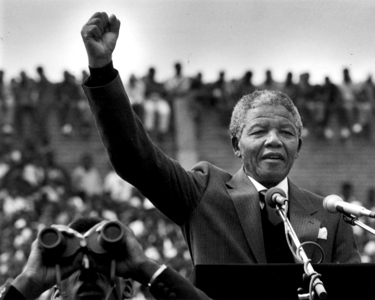 "FEBRUARY 13: Nelson Mandela gestured to supporters in Soweto two days after his release from prison in Cape Town. He addressed more than 100,000 people inside a soccer stadium saying, ""during the past 27 years I have looked forward to this day when I would come back to the area I regard as home, to meet my brothers and sisters and grandchildren."" (Photo by Joanne Rathe/The Boston Globe via Getty Images)"