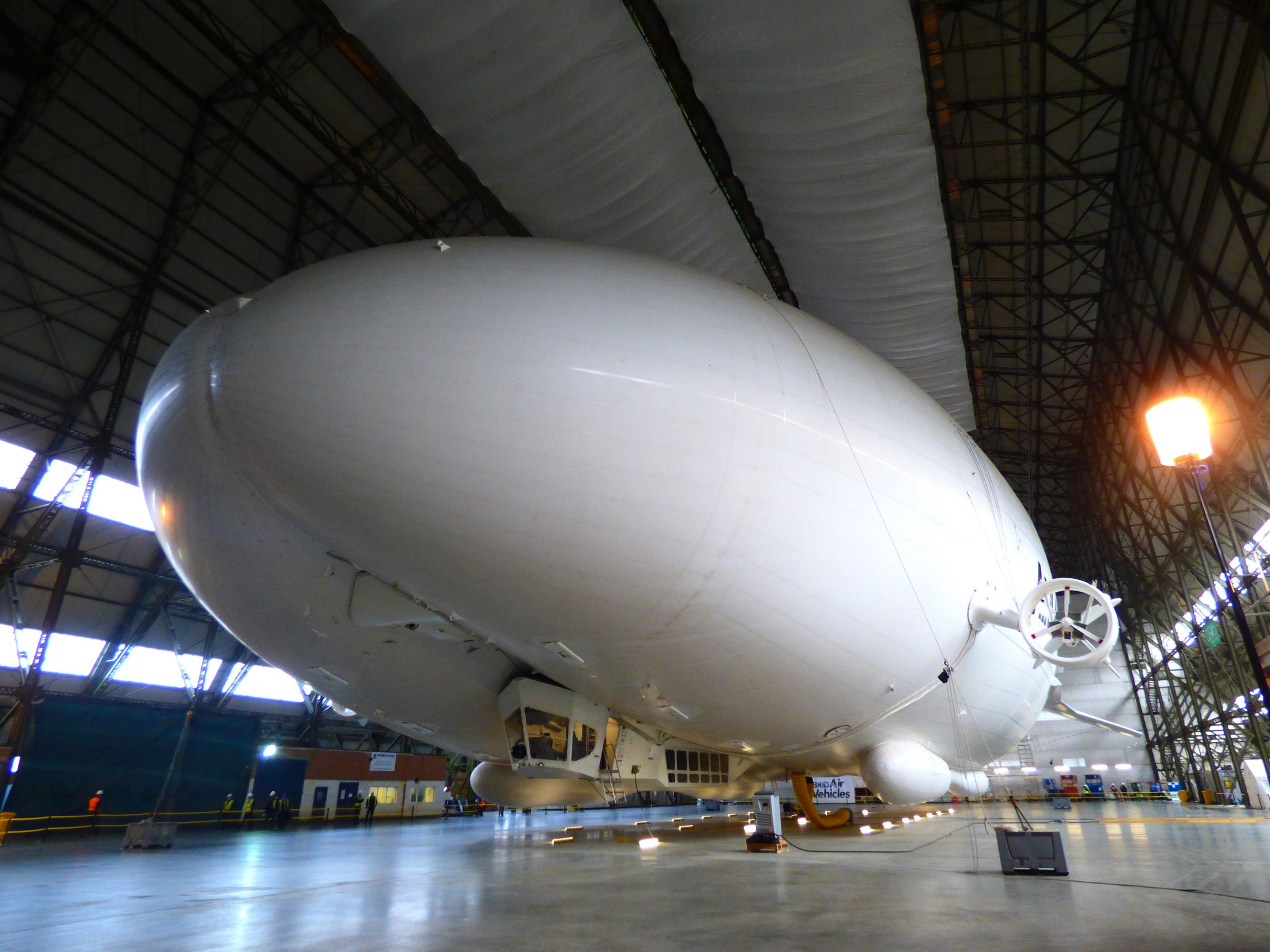 """PICTURE SHOWS: Archive Airlander test flight picture ... STORY COPY: The World???s Largest Aircraft will have a luxurious interior. Hybrid Air Vehicles Limited and Design Q unveiled the Airlander 10 passenger cabin on Wednesday (18 July), showcasing what???s possible in luxury expeditionary tourism in their 'Rethink the Skies' campaign. HAV say: """"Airlander 10???s remarkable passenger cabin opens up new possibilities by approaching air travel from a different perspective. Passengers on Airlander will have luxurious private en-suite bedrooms and will be able to enjoy horizon-to-horizon views in the aircraft???s extensive Infinity Lounge. The Altitude Bar will offer drinks with the ultimate view, while 18 guests can enjoy fine dining in the skies."""" Stephen McGlennan, CEO of HAV, comments that Airlander 10 is changing the way we think about air travel. ???Airlander challenges people to rethink the skies ??? that???s the driving force behind everything we do,??? he says. ???Air travel has become very much about getting from A to B as quickly as possible. What we???re offering is a way of making the journey a joy.??? Airlander 10 can take off and land from virtually any flat surface, eliminating the need for traditional infrastructures like ports or airports. This opens up opportunities for luxury expeditions to places existing transport can???t get to and offers the ultimate in transformative, experiential travel. The new cabin design takes full advantage of Airlander???s unique characteristics to create an environment unlike anything available in aviation today. Design Q???s CEO Howard Guy adds: ???We love doing different things. Our fantastic team of young designers relish the opportunity to do something no one???s done before, to imagine a new concept and then to get into the detailed design of what this space will be.??? Airlander 10???s interior is unusually spacious ??? the cabin is larger than most single-aisle aircraft, such as the A320. This space all"""