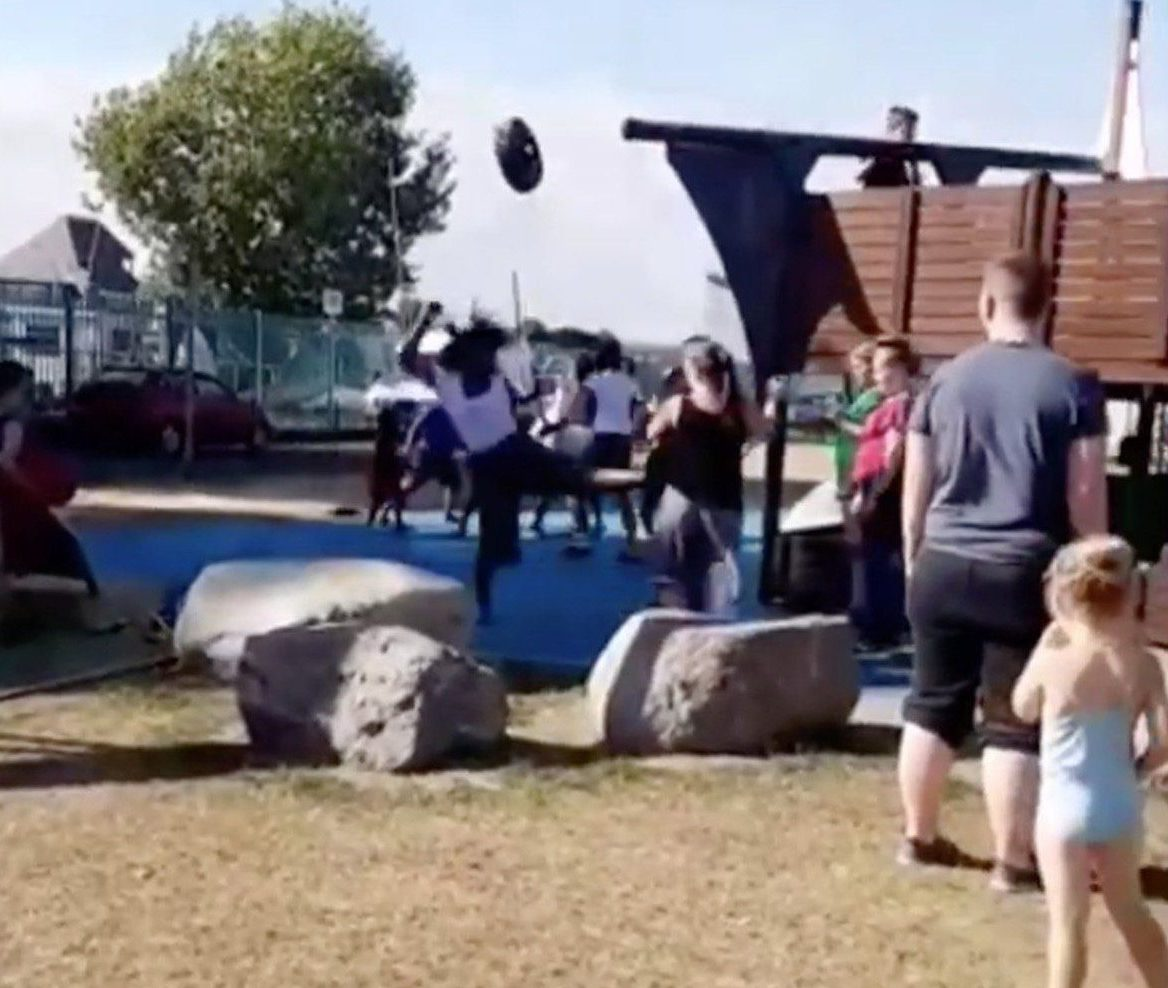 - Image taken of a video of a mass brawl in a school playground in GillinghamLink to video:https://www.dropbox.com/s/zn9wgr0z17dmhp3/School_Brawl_Video_TRIANGLENEWS.MOV?dl=0TRIANGLE NEWS 0203 176 5581 // contact@trianglenews.co.ukA MASS brawl erupted in a school playground in a row over who was next on a zip wire.Parents scattered in horror after several adults and children began brawling in the packed-out park.One mum was led away flanked by two police officers after several patrol cars hurried to the scene.It is understood tempers flared after a child accidentally pushed into the queue to use the zip wire at the Strand in Gillingham, Kent.