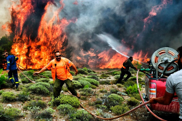 Firefighters and volunteers try to extinguish flames during a wildfire at the village of Kineta, near Athens, on July 24, 2018. Raging wildfires killed 74 people including small children in Greece, devouring homes and forests as terrified residents fled to the sea to escape the flames, authorities said Tuesday. / AFP PHOTO / ANGELOS TZORTZINISANGELOS TZORTZINIS/AFP/Getty Images