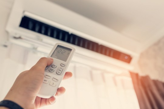 Air conditioner inside the room with woman operating remote controller. / Air conditioner with remote controller; Shutterstock ID 507015844; Purchase Order: -