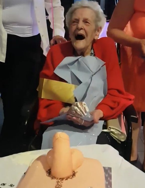 PIC FROM Kennedy News and Media (PICTURED: JEAN ASTLEY, 90, HOWLS IN HORROR AS THE PENIS CAKE SQUIRTS CREAM AT HER) This innocent great-great-granny was left howling with shock and then laughter when her cheeky family urged her to tickle a penis cake they bought for her 90th birthday - only for it to drench her in cream. Haley Goulty, 40, couldn't contain her laughter as she videoed her poor nan Jean Astley, 90, being presented with the realistic-looking birthday cake at her party on Saturday. Hilarious footage shows Jean gazing in disbelief at her graphic phallic cake as daughter Liz Ferrar, 59, places it in front of her to the delight of her watching family. SEE KENNEDY NEWS COPY - 0161 660 8596