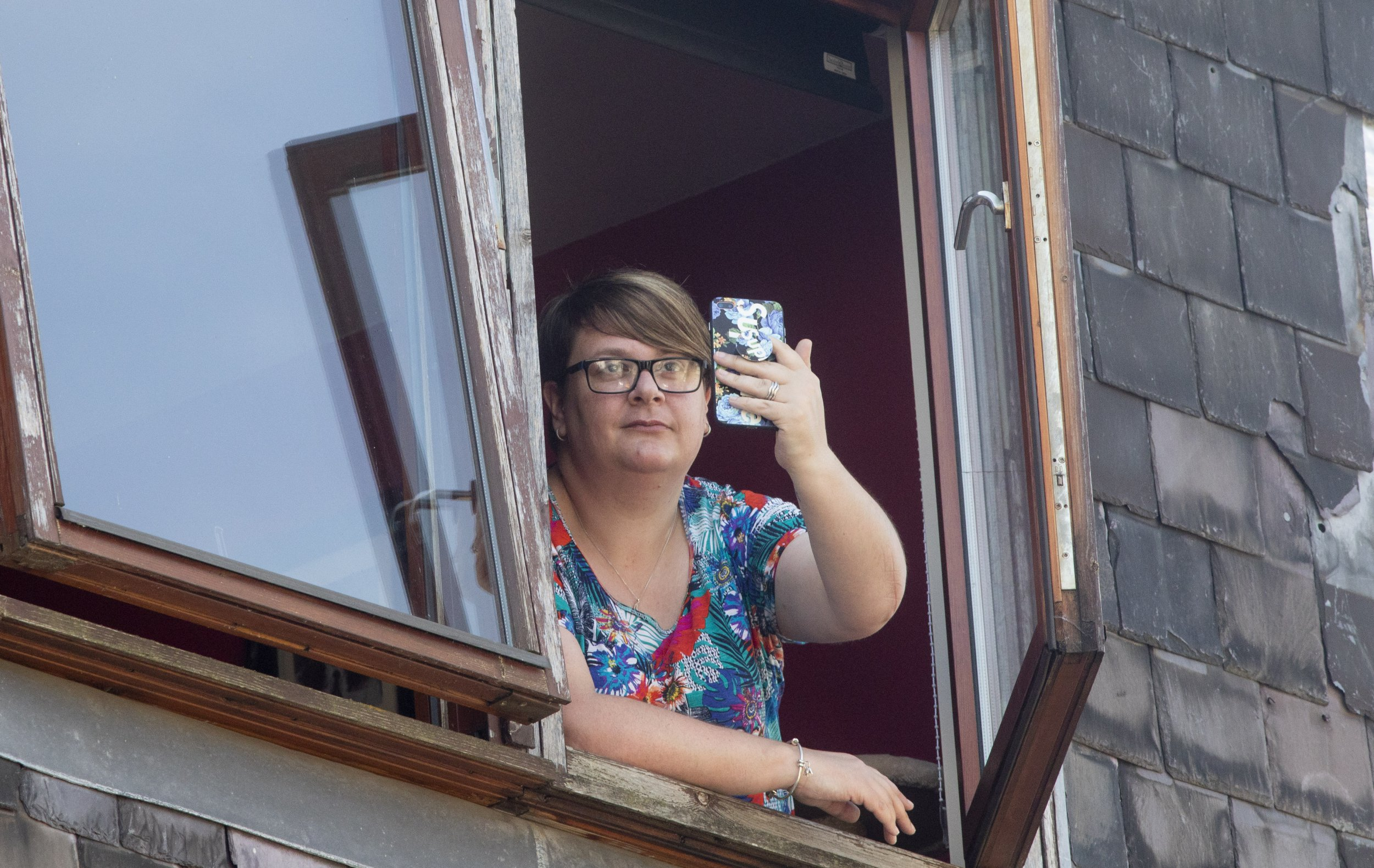 """Tracey Kutluol from Galashiels in the Scottish Borders whose phone was struck by lightening when she was leaning out of her top floor window to film the storm. July 27 2018. See Centre Press story CPLIGHTNING; This is the terrifying moment a women's phone records being struck by a bolt of LIGHTNING - as she tried to film a thunderstorm. Tracey Kutluol was filming the storm from her living room window when her iPhone was zapped by the thunderbolt at 10pm last night (Thurs). The dramatic footage shows Tracey, from Galashiels, Scottish Borders, joking """"I'm going to get electrocuted"""" as she opened her window to get a better look at the storm. The video shows dark clouds and thunder can be heard before a flash of lightning strikes the phone. The mum-of-two, who was with her children Max, ten and Mia, 14, while filming the video, said her life flashed before her eyes."""