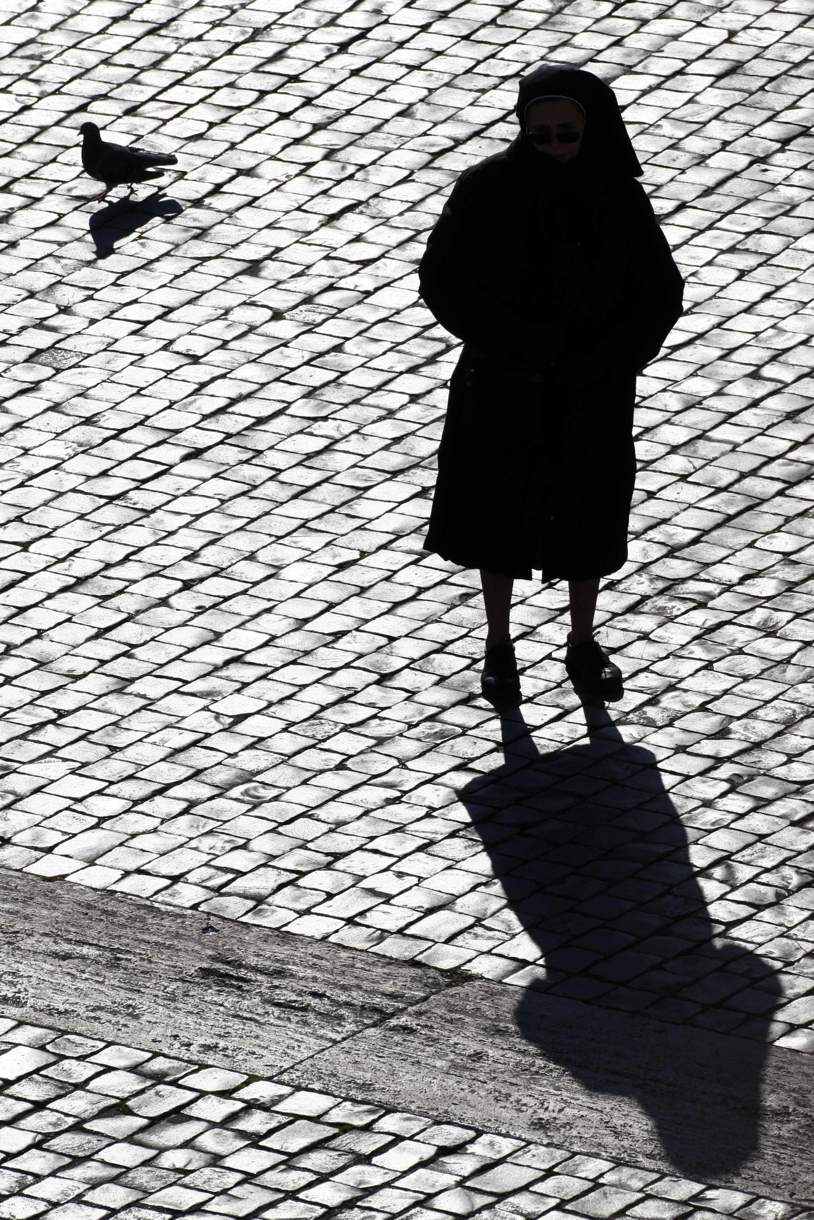 FILE - In this Sunday, Dec. 20, 2009 file photo, a nun is silhouetted in St. Peter's Square at the Vatican. Some nuns are now finding their voices, buoyed by the #MeToo movement and the growing recognition that adults can be victims of sexual abuse when there is an imbalance of power in a relationship. The sisters are going public in part because of years of inaction by church leaders, even after major studies on the problem in Africa were reported to the Vatican in the 1990s. (AP Photo/Pier Paolo Cito, File)
