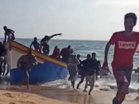 Tourists watch in shock as migrants wash up in boat and rush onto Spanish beach