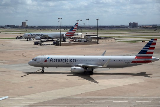 FILE - In this June 16, 2018 file photo, American Airlines aircrafts are seen at Dallas-Fort Worth International Airport in Grapevine, Texas. American Airlines says it will stop using plastic straws and drink stirs and replace them with biodegradable alternatives. American said Tuesday, July 10, 2018, that starting this month in its airport lounges it will serve drinks with straw and wood stir sticks and begin moving to what it called eco-friendly flatware. (AP Photo/Kiichiro Sato, File)