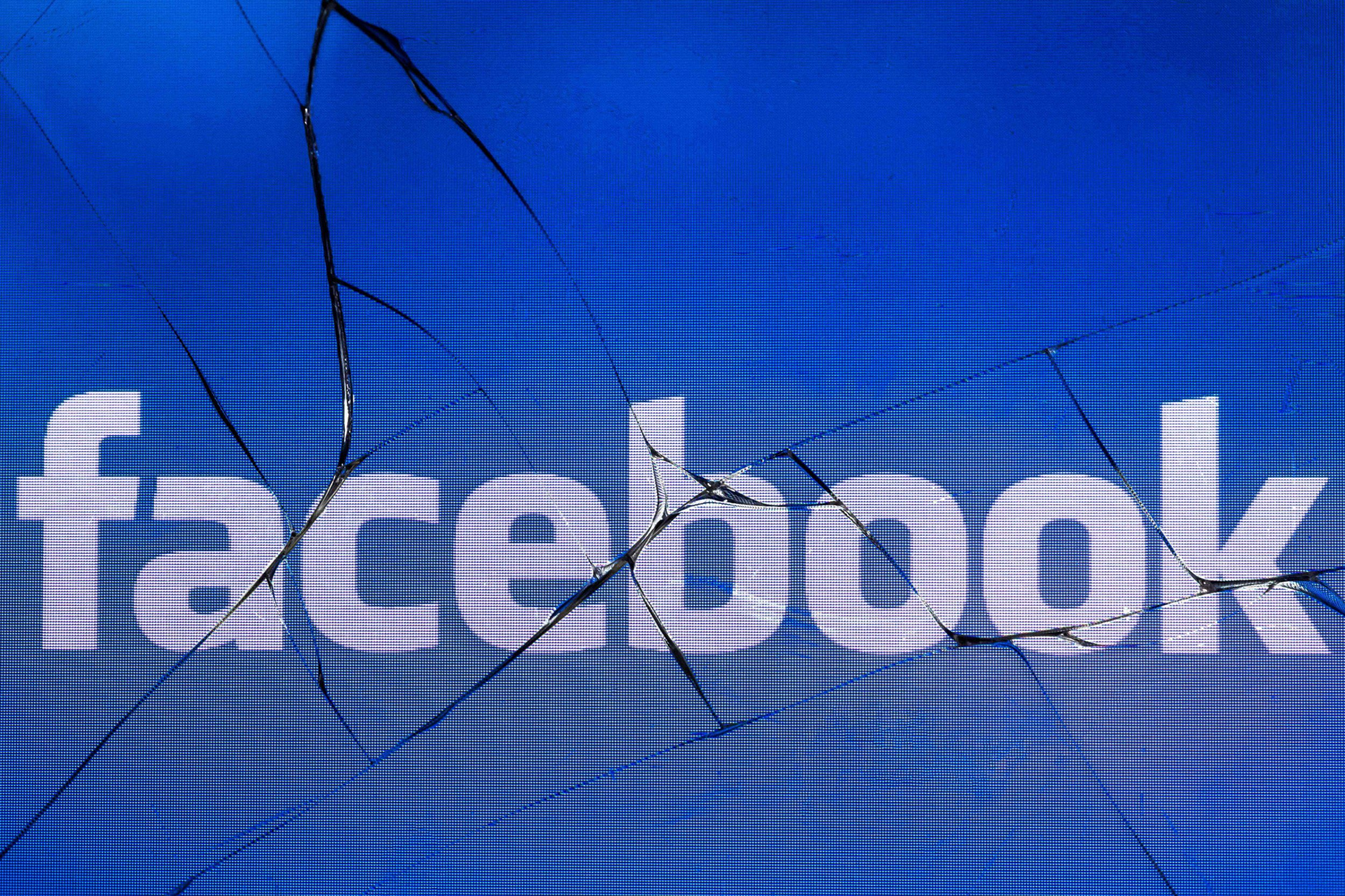 """(FILES) In this file photo taken on May 16, 2018 in Paris shows the logo of the social network Facebook on a broken screen of a mobile phone. Facebook said Tuesday it had shut down more than 30 fake pages and accounts involved in what appeared to be a """"coordinated"""" attempt to sway public opinion on political issues ahead of November midterm elections, but cannot identify the source. / AFP PHOTO / JOEL SAGETJOEL SAGET/AFP/Getty Images"""
