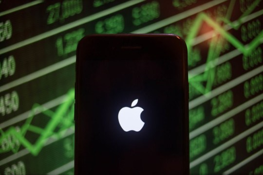 BANGKOK, THAILAND - 2018/07/30: An iPhone displays the Apple logo with a background of a market value increasing on the stock exchange behind. (Photo by Guillaume Payen/SOPA Images/LightRocket via Getty Images)