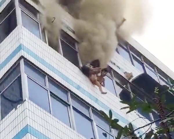 Pic shows: The siblibs being rescued by their mother A mother in China has died shortly after she was seen in this video saving her two children by throwing them from the window of her burning 5th floor home to be caught by rescuers below. But the unnamed mother was unable to escape the blaze and was declared dead by doctors at Xuchang People???s Hospital in East China???s Jiangsu province. Footage of the blaze in Xuchang???s Weidu district shows pedestrians staring up at the woman standing in the window of her burning home, from which plumes of smoke are spewing into the air. The mum had screamed for help and threw blankets onto the street below, witnesses said. Passers-by grabbed the quilts and duvets and urged the woman to throw her children down to them. The video shows the woman mustering up all the strength left in her to drop first her nine-year-old son and then her three-year-old daughter, both of whom are caught by rescuers below. The blaze rages on as the woman lies out of breath at the top of the building, ultimately passing out on the windowsill. Reports said the woman???s children were taken to hospital and are in a stable condition. Her daughter suffered a broken leg during the rescue and is to undergo surgery. The hospital declared the mother dead after efforts to revive her were unsuccessful. The cause of the fire still unknown.