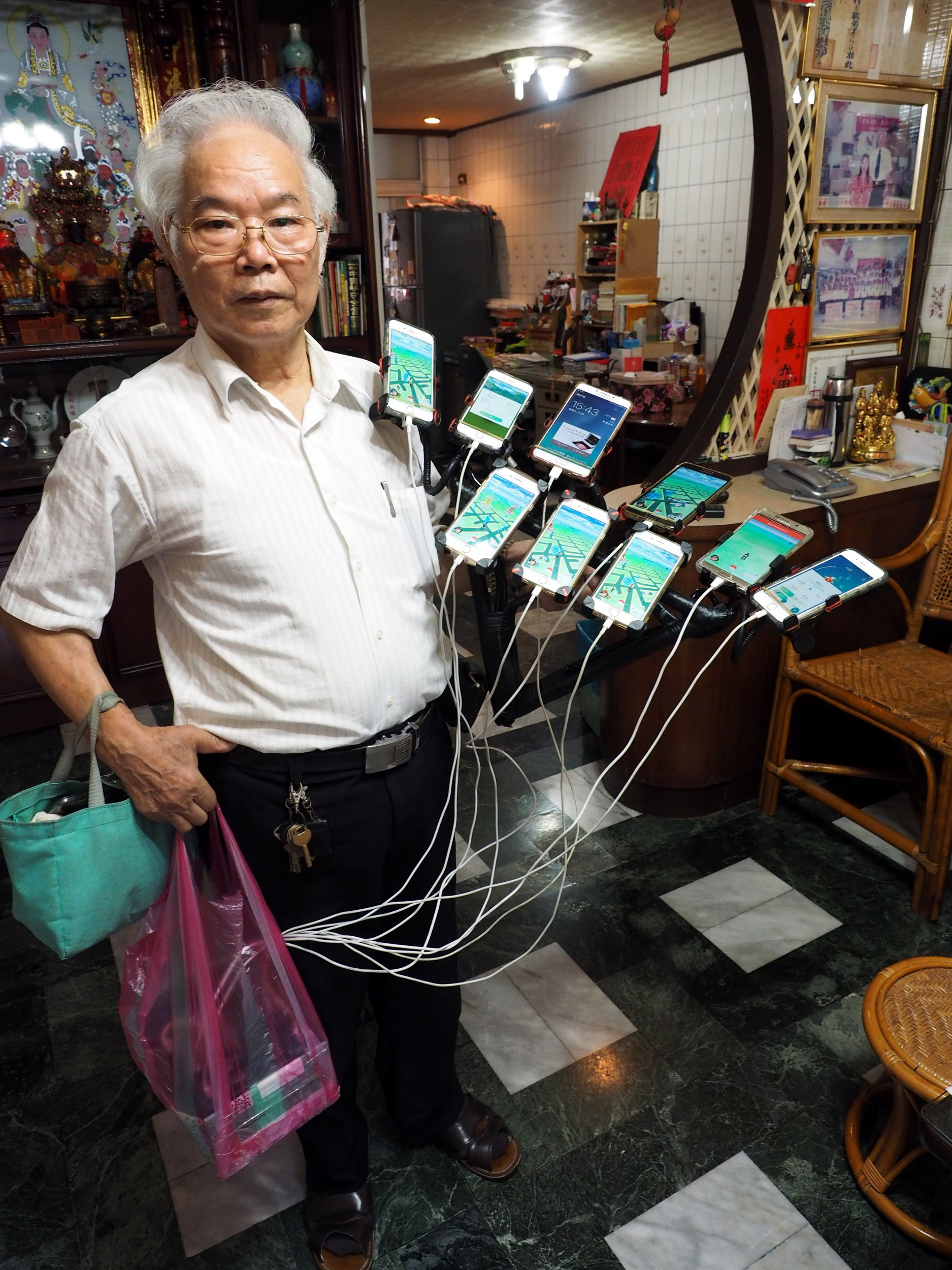 epa06935284 Chen San-yuan, a 59-year-old Feng Shui Master, carries 11 cellphones on a frame and a bag of batteries to go to catch Pokemon in New Taipei City, Taiwan, 08 August 2018. Chen was hooked on Pokemon Go in 2016 when his grandson taught him how to play the game. Now he has mounted 11 cellphones on his bike, charged by a bag of batteries, and spends all his spare time catching Pokemon on streets or in parks, sometimes staying outside until 4 am. Chen wants to increase his cellphones to 15. After TV reported him, Chen has become a celebrity. Many people call him 'Uncle Pokemon' and take photos with him. EPA/DAVID CHANG