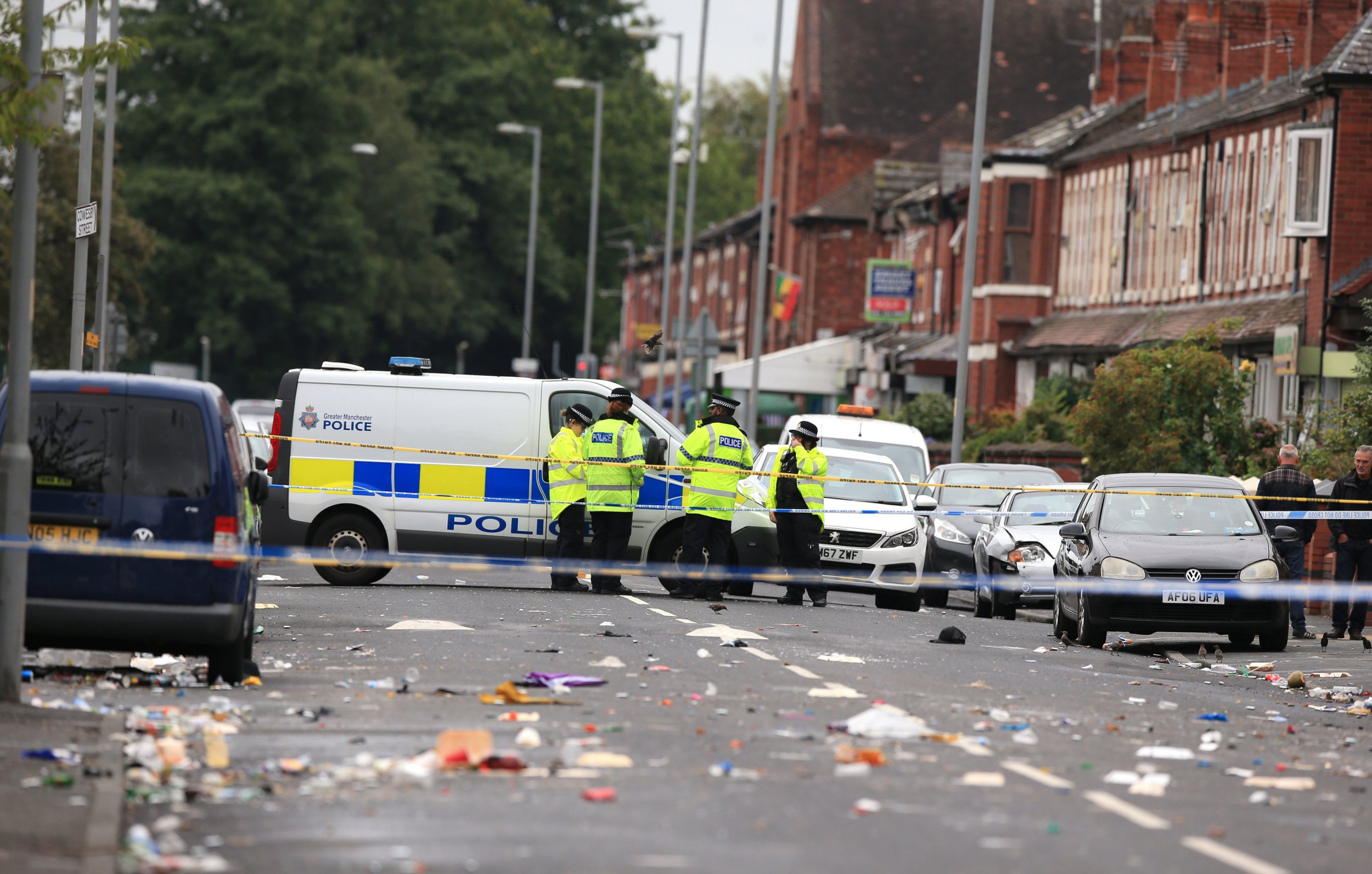 Police officers at the scene in Claremont Road, Moss Side, Manchester, where ten people, including two children were taken to hospital after reports of gunshots at a street party. PRESS ASSOCIATION Photo. Picture date: Sunday August 12, 2018. Armed officers were called at 2.30am on Sunday following the celebrations of the Caribbean Carnival. One man was in a serious but stable condition with leg injuries and nine others, were taken to hospital with pellet-type wounds. See PA story POLICE Shooting. Photo credit should read: Peter Byrne/PA Wire