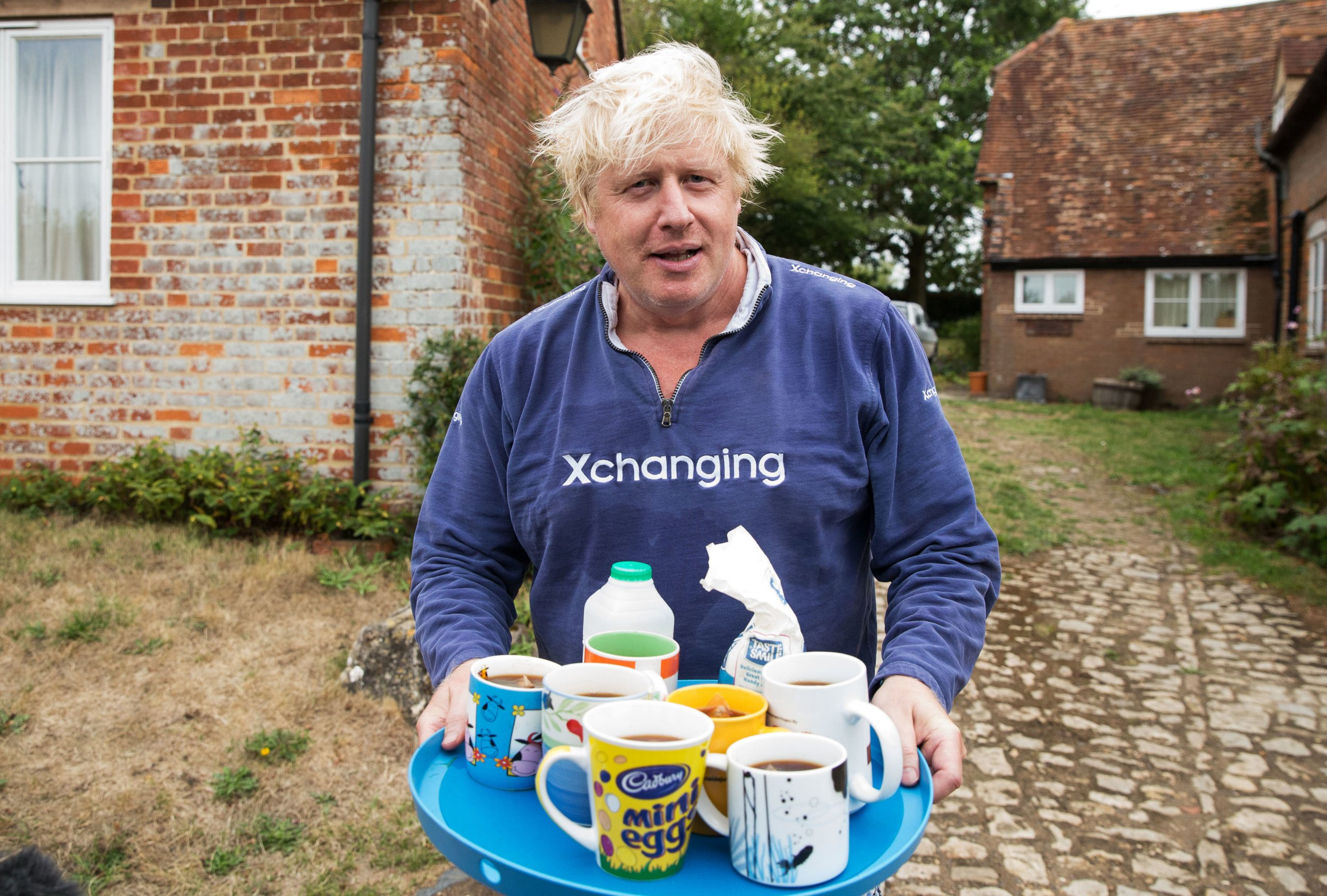 Boris Johnson brings tea for the press to drink outside his house in Thame. PRESS ASSOCIATION Photo. Picture date: Sunday August 12, 2018. See PA story POLITICS Johnson. Photo credit should read: Aaron Chown/PA Wire