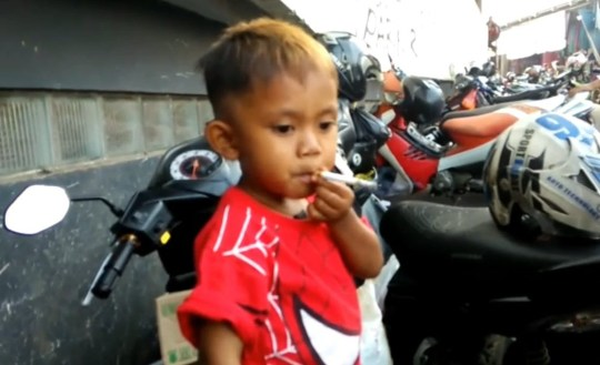 VIDEO STILLS - This chain-smoking toddler has developed a insatiable habit - and puffs through 40 a DAY. Two-and-a-half year old Rapi Ananda Pamungkas started by picking up used butts outside his mum's market stall in Sukabumi, Indonesia. But within days he was hooked - and would constantly pester passing adults to give him cigarettes. Adults initially found the youngster's demands endearing and plied him with cigarettes while laughing as he lit up. But Rapi - nicknamed Rap - soon started becoming aggressive and throwing tantrums when he couldn't get his beloved ''meroko'', the local term for smokes. Rapi's mother, Maryati, 35, admitted on Monday (13/08) that she buys cigarettes for the boy to stop him from going ''beserk''.