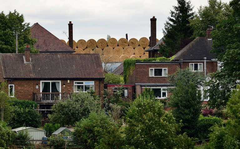 GV of the hay bales in the village of Ockbrook in Derbyshire, where residents have been left shocked by a huge stack of hay bales dumped right next to their homes. 15 August 2018. See NTI story NTIBALES; Villagers have been left stunned after 30 tonnes of hay bales were left towering above their homes. The 30ft-high stacks were left in a field adjacent to the back gardens of ??500,000 detached properties. Resident Peter Shaw, 55, noticed the bales which were left stacked behind his house on Cole Road, Ockbrook, Derbys., last Thursday (9/8). The villagers believe they were put there deliberately after a planning application by a farmer to run a waste processing site was rejected. Mr Shaw and his wife Helen, 50, moved into the home in 2004, and say they have never had a problem with the famer, Richard Barton, before. But Mr Shaw, who works in the motoring trade, says the bales are a potential fire risk.
