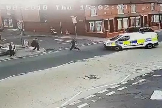 This is the moment a police officer was hit by a colleague?s van as he chased suspect. The officer was taken to hospital for treatment to leg injuries following the incident near Mandley Park, Higher Broughton, Manchester. Footage shows a police van pulling up at the junction of Leicester Road and Symons Street. An officer jumps out and starts to pursue a man standing on the pavement, but as the Greater Manchester Police patrol follows the pair onto Symons Street, the officer on foot is hit by the van.