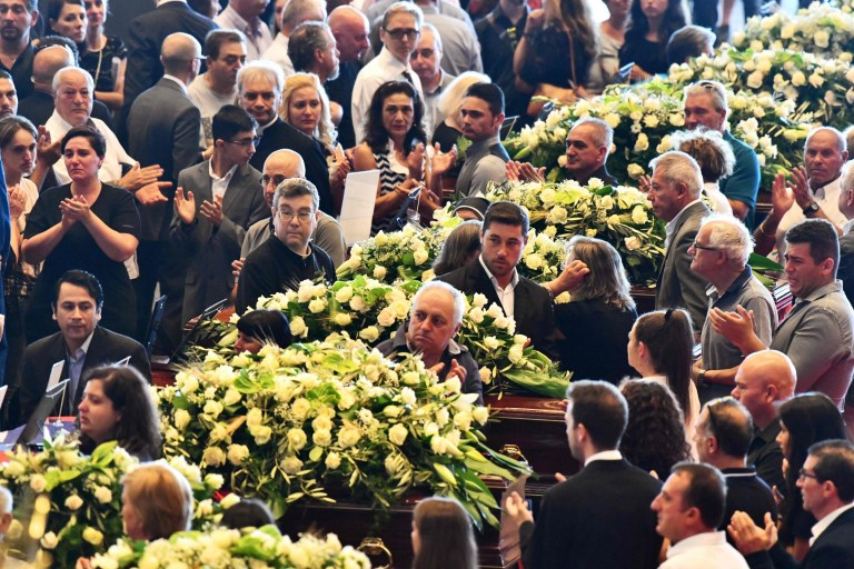 Relatives standing next to the coffins of some of the victims of the collapsed Morandi highway bridge, laid in front of the altar, applaud at the start of the funeral service, in Genoa, on August 18, 2018. - Fury is growing over the shock collapse of the Morandi bridge, a decades-old viaduct that crumbled in a storm on August 14 killing at least 38 people, with Italian media reporting that some outraged families would shun August 19's official commemorations. (Photo by Andrea LEONI / AFP)ANDREA LEONI/AFP/Getty Images