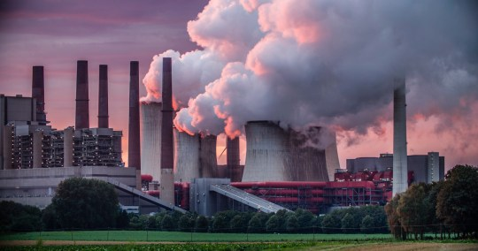 Industry in dramatic red sunset light. Chimneys and cooling tower of a coal fired power station.