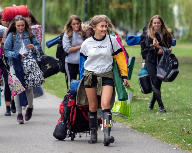 Festival goers walking with their camping equipment as they arrive for Reading Festival