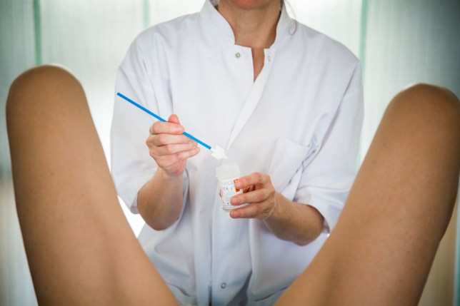 Gynecologist performing a cervical smear or pap test on a patient.