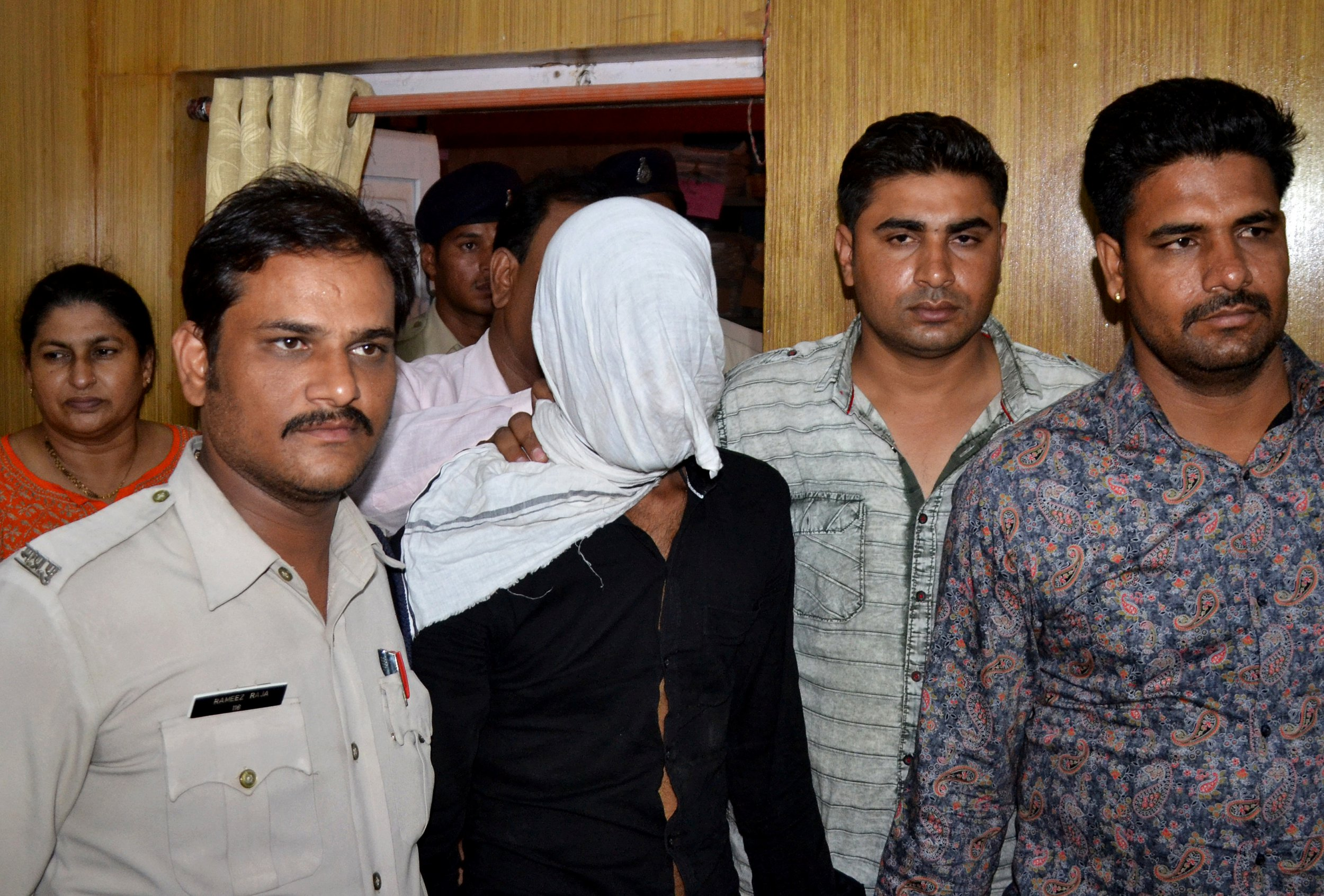 Plain-clothes police officers escort Irfan (face covered), who is accused of rape of a seven-year-old girl, as he is presented in front of the media in Mandsaur, India, June 27, 2018. Picture taken on June 27, 2018. REUTERS/Stringer - RC19AED63C90
