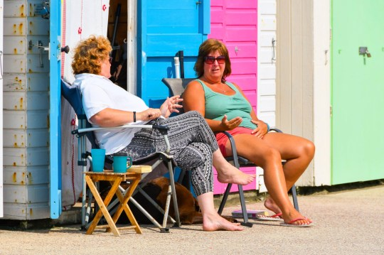 Alamy Live News. PGK304 Lyme Regis, Dorset, UK. 27th August 2018. UK Weather. Two women reading outside a seafront beach hut as they enjoy the warm sunny spells at the seaside resort of Lyme Regis in Dorset on Bank Holiday Monday after Sunday was a washout. Picture Credit: Graham Hunt/Alamy Live News This is an Alamy Live News image and may not be part of your current Alamy deal . If you are unsure, please contact our sales team to check.