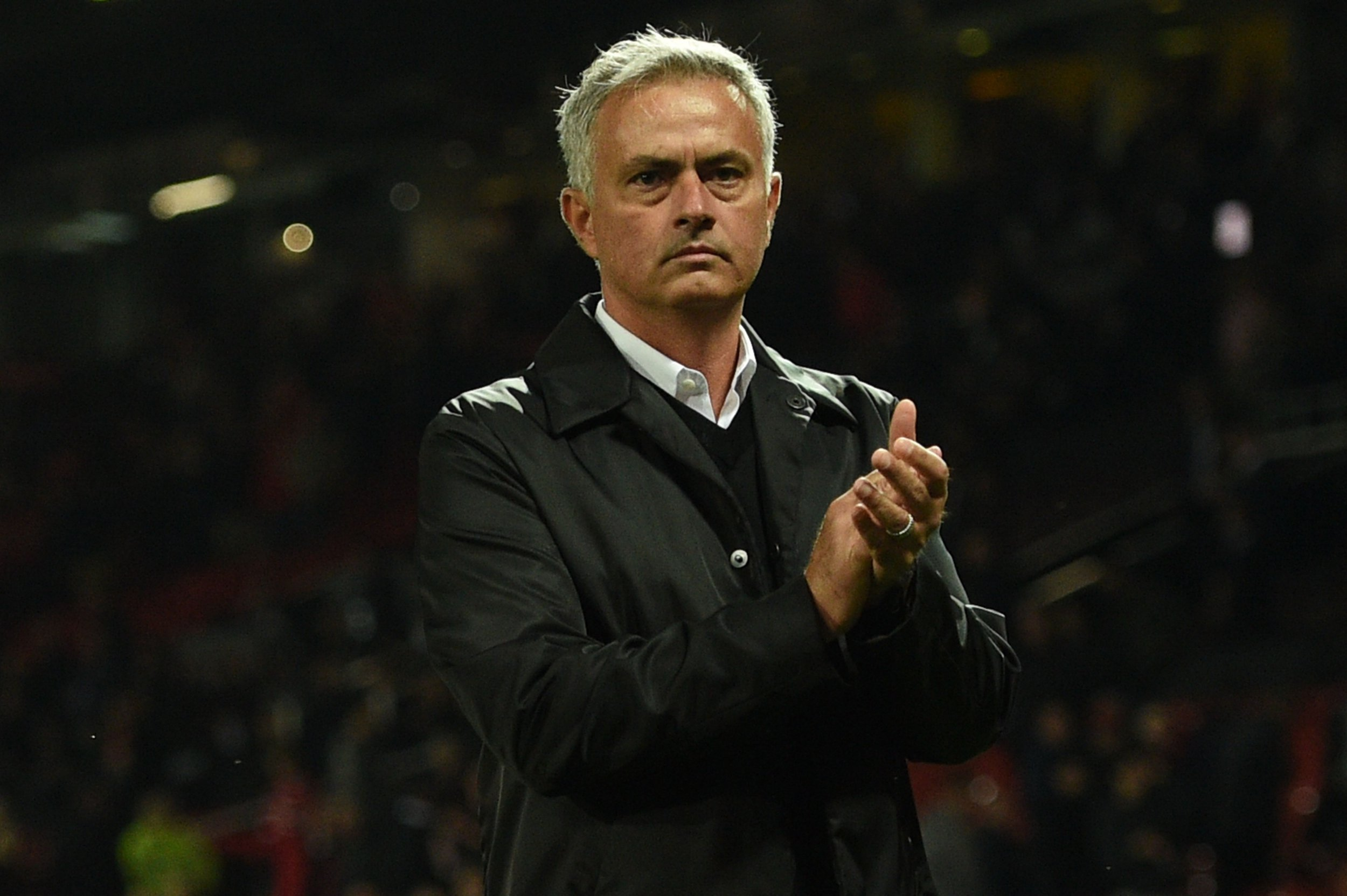 Manchester United's Portuguese manager Jose Mourinho stands on the pitch applauding the homes fans that stayed until the end after the English Premier League football match between Manchester United and Tottenham Hotspur at Old Trafford in Manchester, north west England, on August 27, 2018. (Photo by Oli SCARFF / AFP) / RESTRICTED TO EDITORIAL USE. No use with unauthorized audio, video, data, fixture lists, club/league logos or 'live' services. Online in-match use limited to 120 images. An additional 40 images may be used in extra time. No video emulation. Social media in-match use limited to 120 images. An additional 40 images may be used in extra time. No use in betting publications, games or single club/league/player publications. / OLI SCARFF/AFP/Getty Images