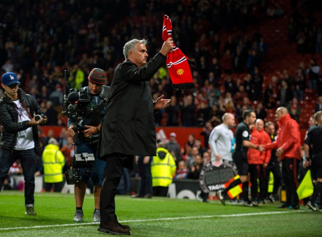 epa06977370 Manchester United manager Jose Mourinho reacts with a Manchester United scarf thrown from the crowd after the English Premier League soccer match between Manchester United and Tottenham at the Old Trafford in Manchester, Britain, 27 August 2018. EPA/PETER POWELL