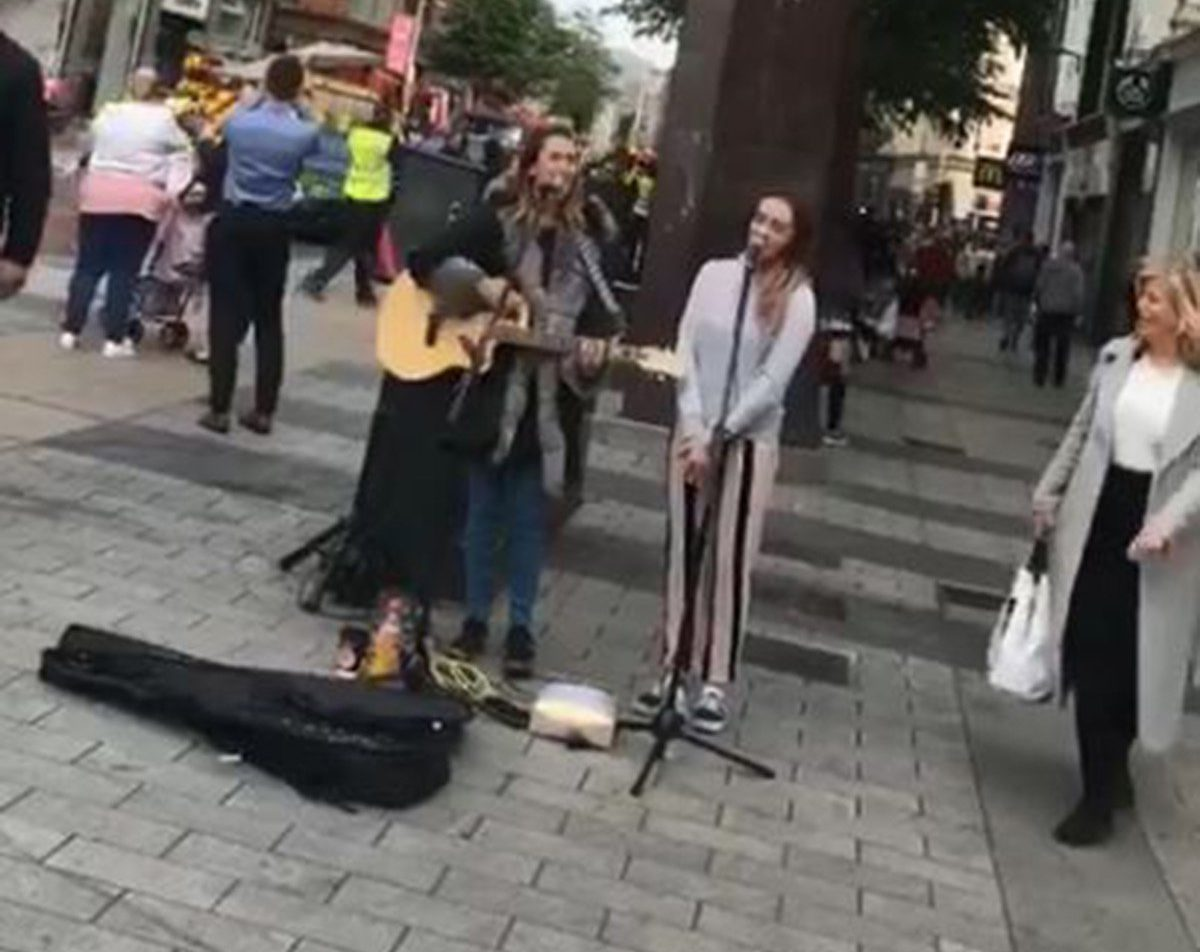 Busker chooses wrong song to sing in front of Primark as it burns in Belfast