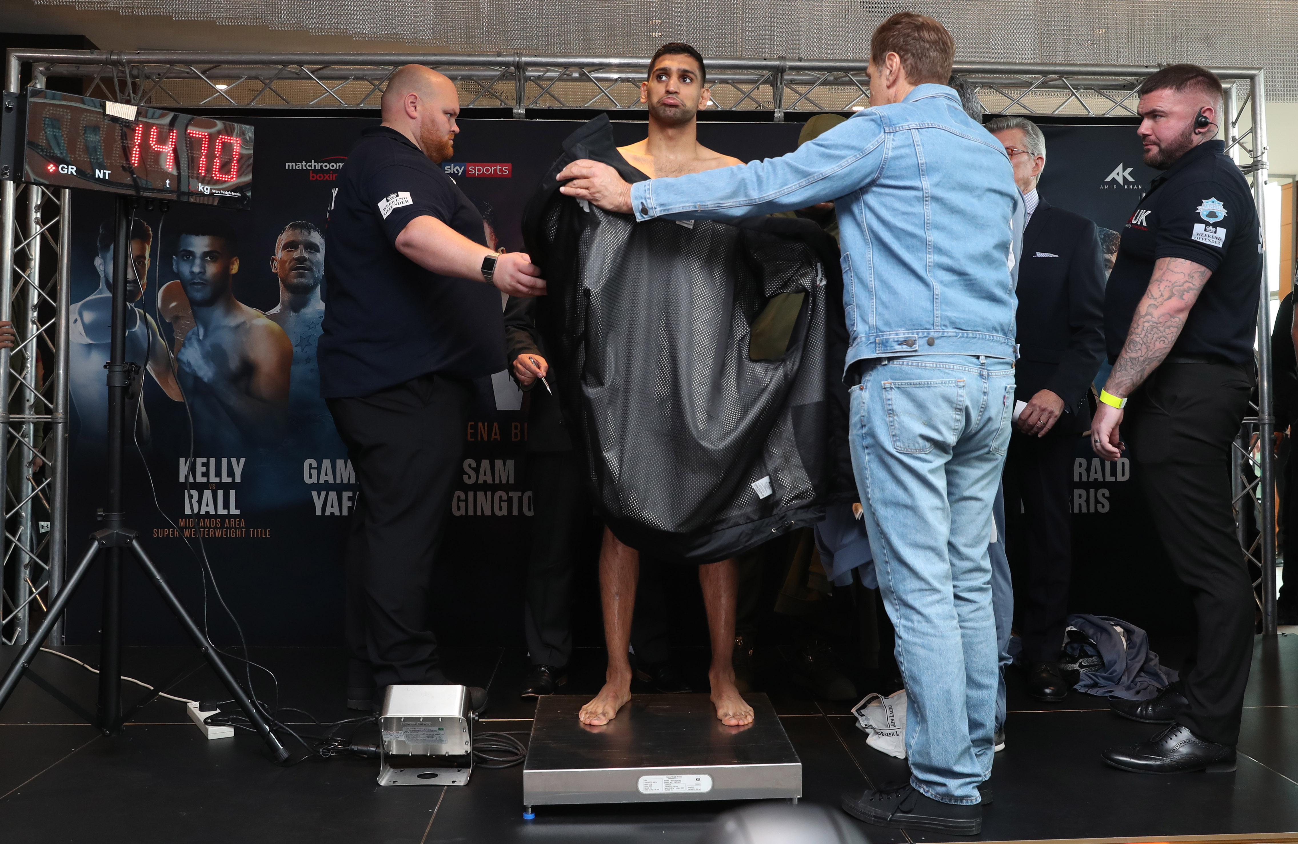 Amir Khan weighs in with the help of a coat to make welterweight for Samuel Vargas clash