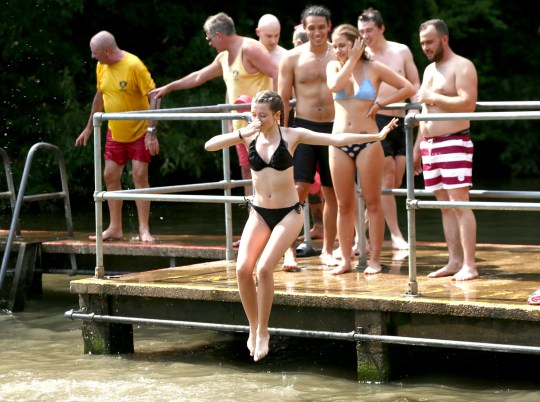 People sunbathing at the mixed bathing pond on Hampstead Heath, London, as heatwave conditions continue across much of England. PRESS ASSOCIATION Photo. Picture date: Thursday July 26, 2018. See PA story WEATHER Hot. Photo credit should read: Yui Mok/PA Wire