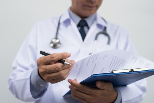 Male doctor on duty in white coat reading patient's information with pen in hand, filling prescription or checklist document, close up, selective focus on pen, health and medical concept.; Shutterstock ID 500410051; Purchase Order: -