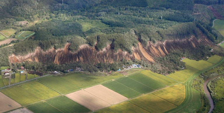 This aerial photo shows the site of a landslide after an earthquake in Atsuma town, Hokkaido, northern Japan, Thursday, Sept. 6, 2018. A powerful earthquake rocked Japan???s northernmost main island of Hokkaido early Thursday, triggering landslides that crushed homes, knocking out power across the island, and forcing a nuclear power plant to switch to a backup generator. (Kyodo News via AP)