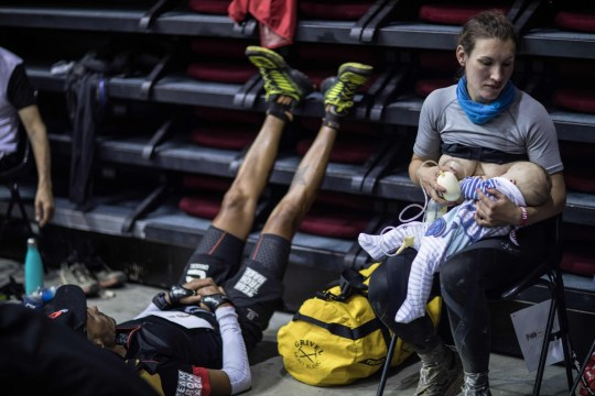 """Great-Britain's trail runner Sophie Power breastfeeds her three months old baby Cormac during a break as she competes in the 170 km Mount Blanc Ultra Trail (UTMB) race on August 31, 2018 in Courmayeur. - The 16 th Ultra-Trail du Mont-Blanc (UTMB), a mountain ultramarathon with numerous passages in high altitude (>2500m) and in difficult weather conditions (night, wind, cold, rain or snow), takes place once a year around the Mont-Blanc across French, Italian and Switzerland's Alps. (Photo by Alexis BERG / Mons Prod pour Strava / AFP) / RESTRICTED TO EDITORIAL USE - MANDATORY CREDIT """"AFP PHOTO / Mons Prod pour Strava / Alexis BERG"""" - NO MARKETING NO ADVERTISING CAMPAIGNS - DISTRIBUTED AS A SERVICE TO CLIENTS ---ALEXIS BERG/AFP/Getty Images"""