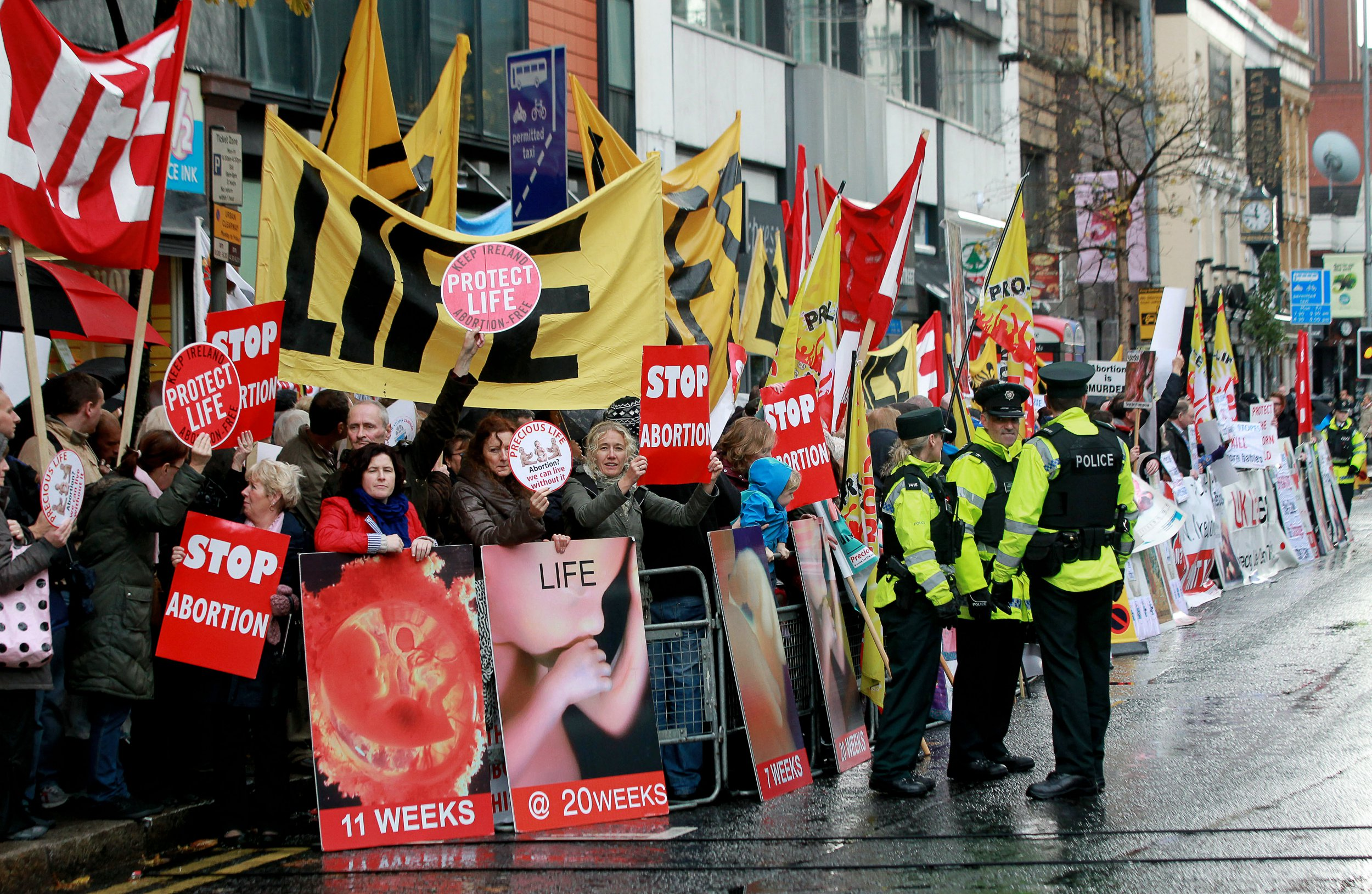 """Police walk around abortion protestors holding up placards outside the Marie Stopes clinic, the first private clinic to offer abortions to women in Belfast, Northern Ireland on October 18, 2012. Dozens of pro-life campaigners protested outside the first abortion clinic in Northern Ireland as it opened to the public. Around 50 protesters brandishing placards saying """"Life is precious"""" and showing photographs of foetuses gathered outside the privately run clinic in an anonymous building in Belfast. AFP PHOTO/ Peter Muhly (Photo credit should read PETER MUHLY/AFP/Getty Images)"""
