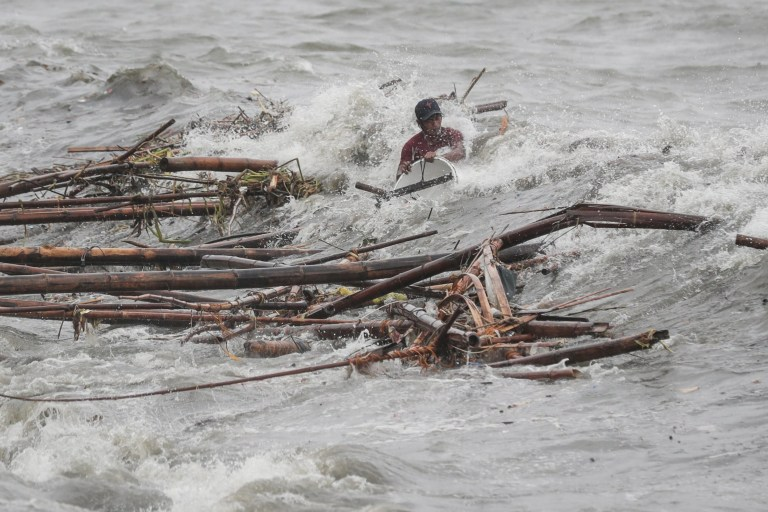 epa07021459 A man is hit by a wave while attempting to recover salvageable materials in Manila Bay, Manila, Philippines, 15 September 2018. Mangkhut, the most powerful typhoon to strike the Philippines in the last five years, made landfall in the northeastern town of Baggao with maximum sustained winds of 205 km/h (128 mph) and gusts of up to 285 km/h (177 mph). The Category 5 storm came ashore at 1:40 am (17:40 GMT on 14 September) in Cagayan province, the Philippine Atmospheric, Geophysical, and Astronomical Services Administration (PAGASA) said. Mangkhut, denoted Ompong in the Philippines, is moving west-northwest at 35 km/h and is expected to exit the archipelago in the direction of Hong Kong late 15 September, according to the PAGASA bulletin. Forecasters said that coastal areas in the impact zone could experience a storm surge of as much as 6 meters. EPA/MARK R. CRISTINO
