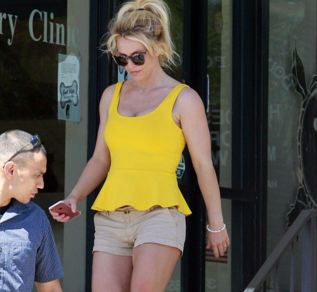 EXCLUSIVE. Coleman-Rayner Los Angeles, CA, USA. September 15, 2018 Britney Spears heads to a Saturday tanning session near her home in Los Angeles. The pop star ? who was escorted to the salon by a male companion ? wore a yellow tank top, beige shorts, brown sandals and shades. She also had a gold band on her wedding finger, and a scar was visible on her left leg. CREDIT MUST READ: Coleman-Rayner Tel US (001) 310 474 4343 - office www.coleman-rayner.com