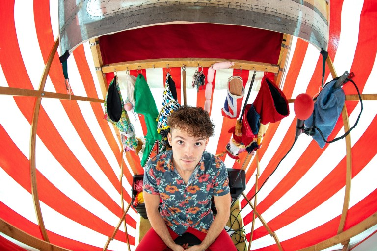 Entertainer WILL COUSINS from Salford inside his Punch and Judy stall , which was built for him by his father , at All Hallows Church in Cheadle . Photo credit: Joel Goodman