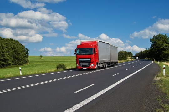 Red truck driving on asphalt road in a rural landscape. White truck coming from afar. Sunny summer day with blue skies and white clouds.; Shutterstock ID 385555642; Purchase Order: -